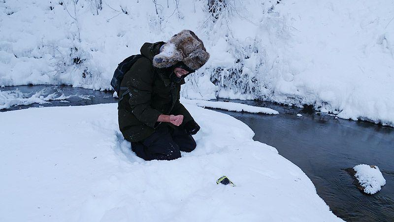 雪原でしゃがみ込み手をおさえて痛がる地主
