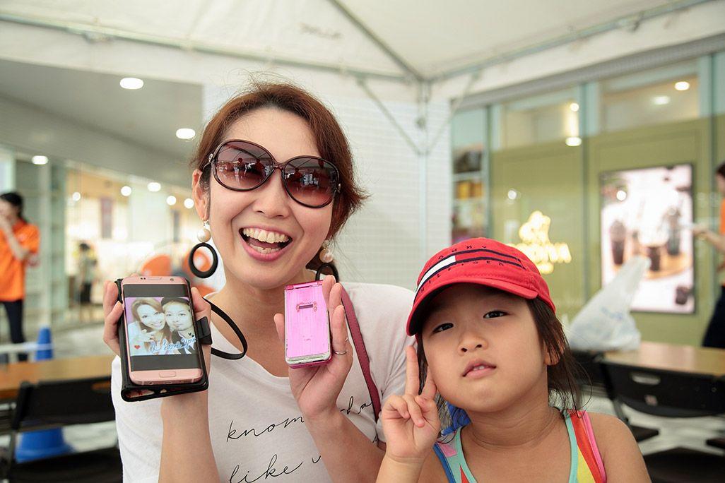 夫との古いツーショットのシールを掲げる笑顔の女性と娘さん