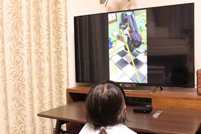 スマホとミラーリングされたテレビを見る娘
