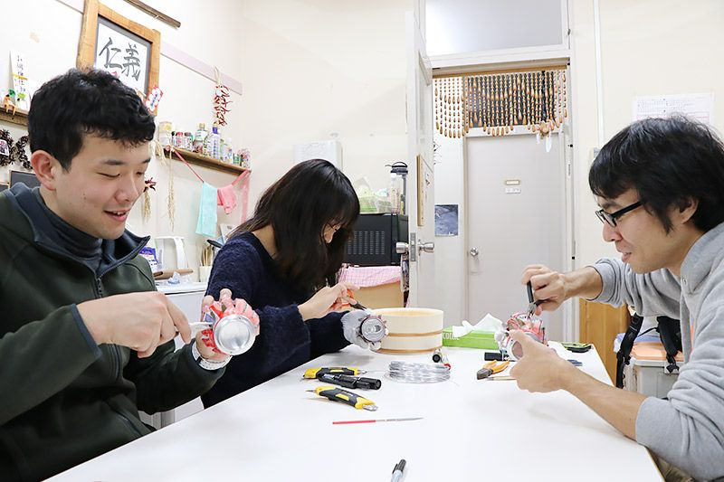 空き缶を切って工作している2人の男性と1人の女性
