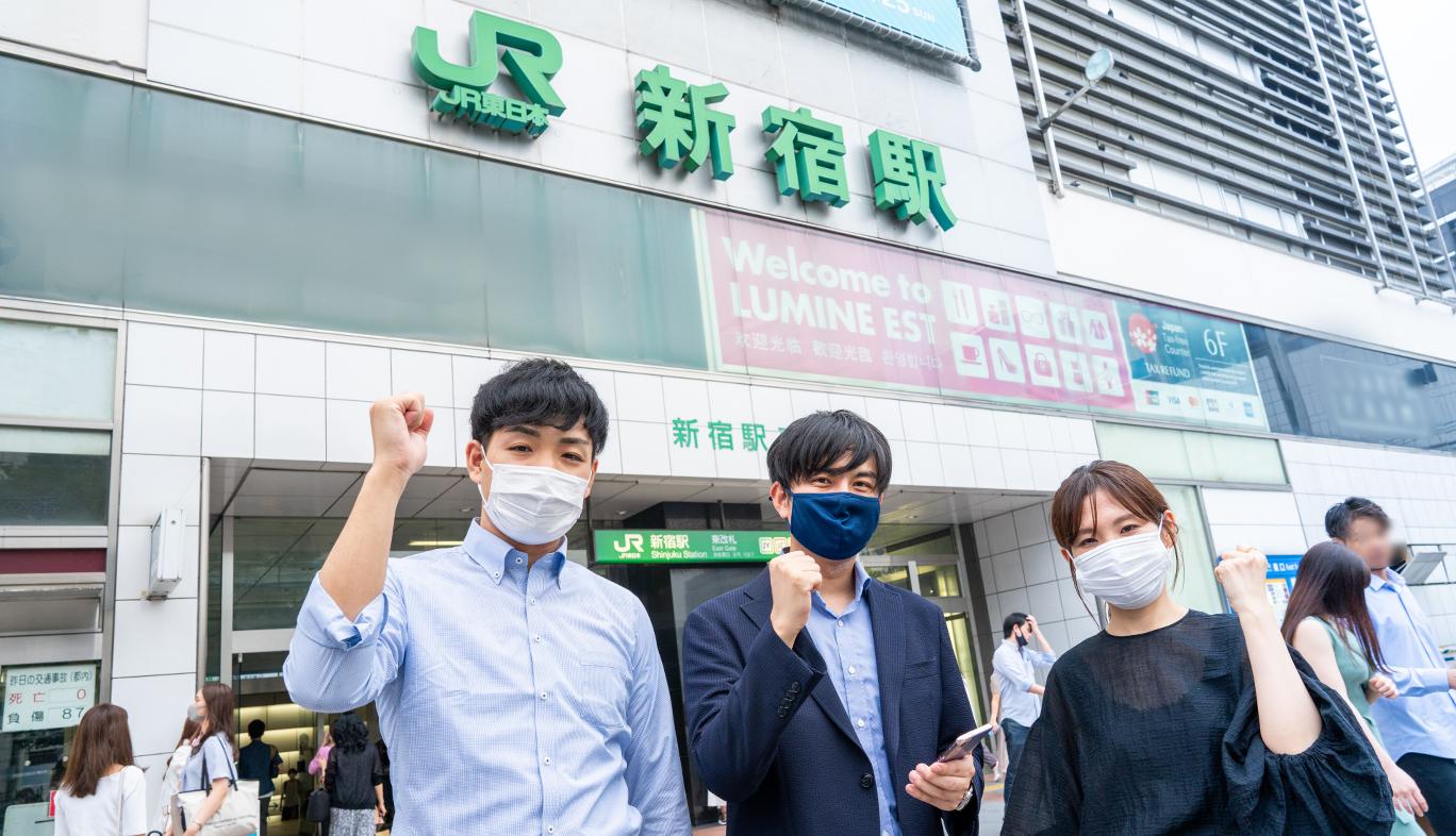 新宿駅東口でau5Gの通信エリアを調査をする人
