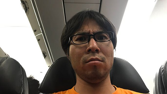 飛行機内での地主の顔アップ