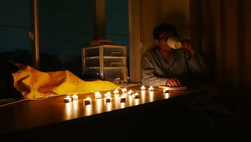ろうそくの光の中、白湯を飲む地主