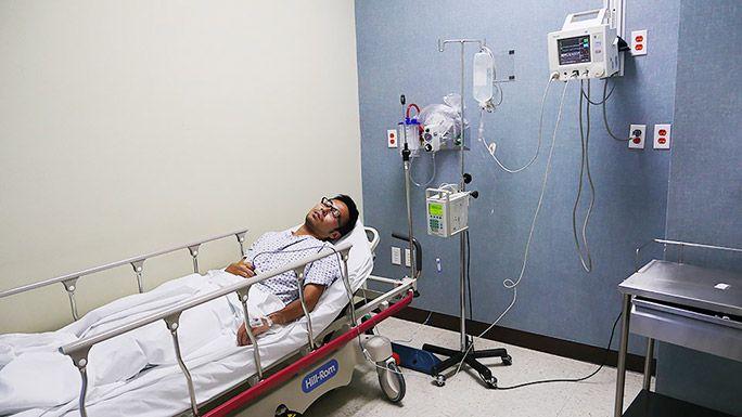 病院のベッドに横たわる地主