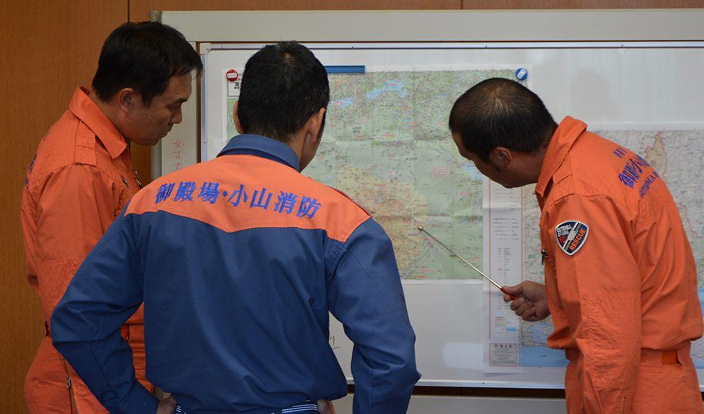 対象地域のマップを見ながら、救助プランを立案。人力で山に入るコースとドローンの飛行コースを同時に考える