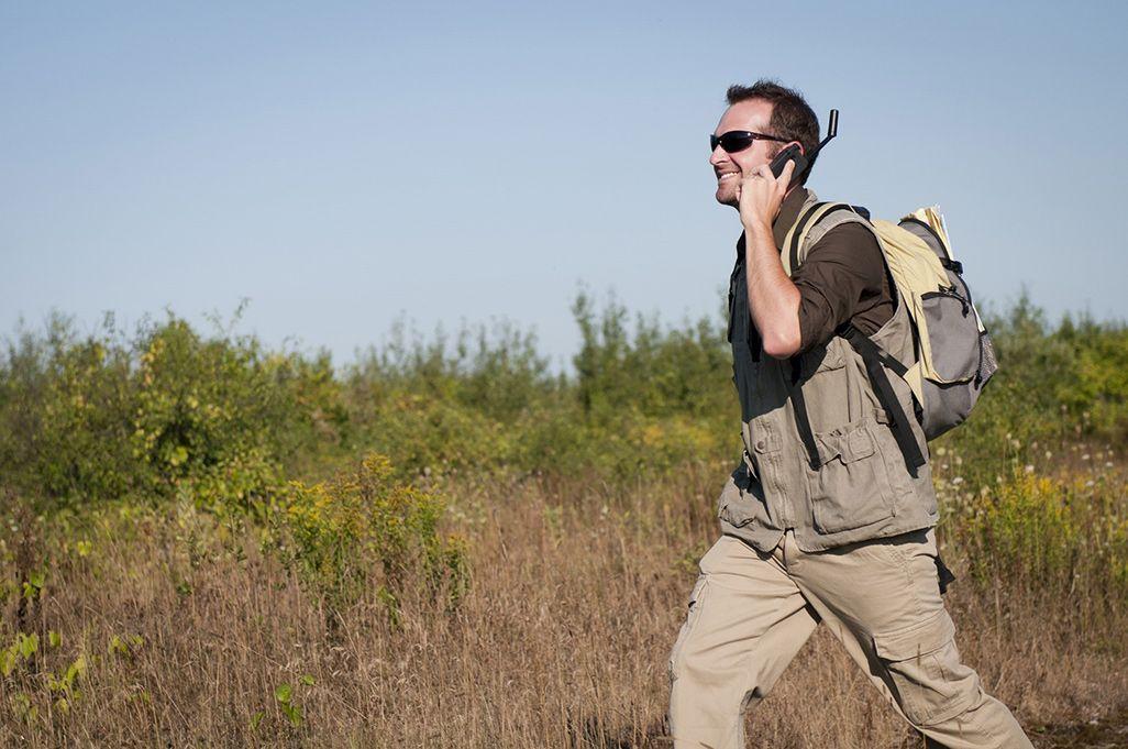 イリジウムで通話しながら歩く男性