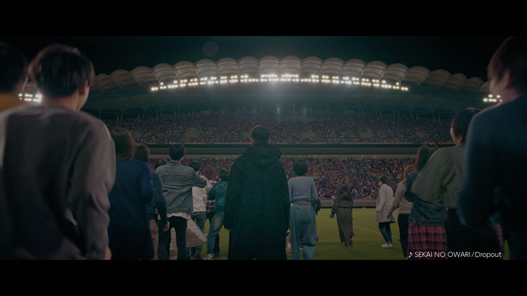 人々とともにサッカースタジアムを目指す松田翔太演じるマツダ