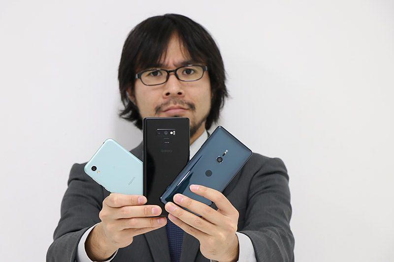 3つのスマートフォンを持ってこちらに見せてくる地主