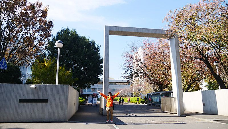 大学の門の前でポーズをとるライターの地主恵亮