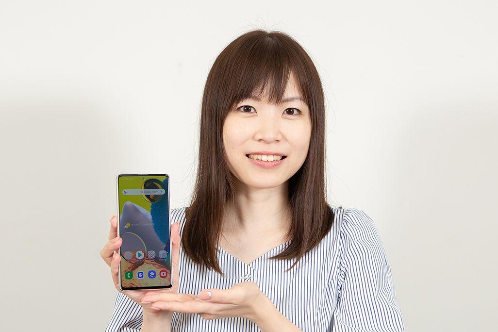 Galaxy A51 5Gを手に持ったKDDI広報部の女性