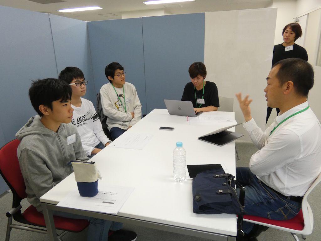 中学生たちのインタビューを受けるKDDIの新井田統
