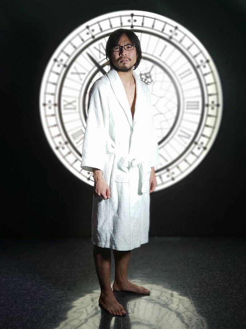 時計を模した照明をバックにバスローブを着た地主