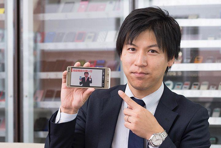 スマホの健康診断/かざして診断カードを説明するauの広報担当の小谷元樹