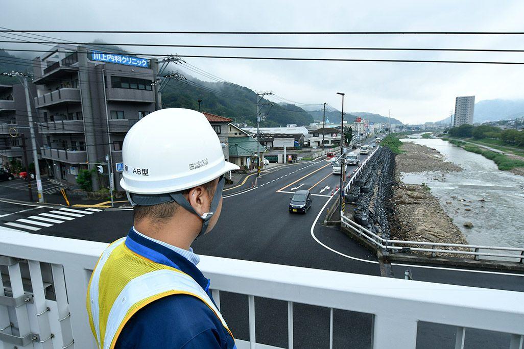 国道のと川を眺める作業着姿の男性