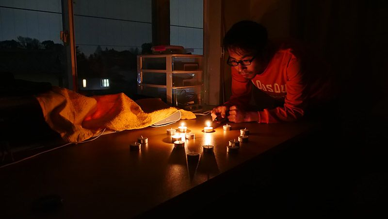 電気を消した自室で複数のろうそくに火をつける地主