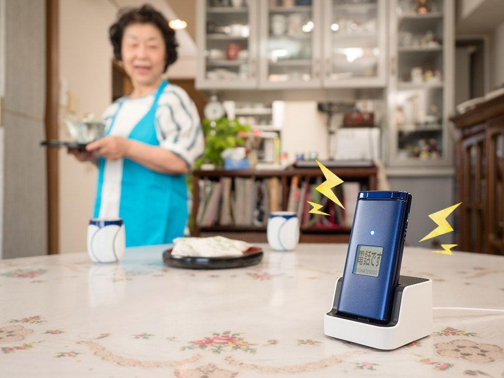 卓上ホルダで充電中の、高齢者向けのケータイ「かんたんケータイ KYF38」で通話する夫婦