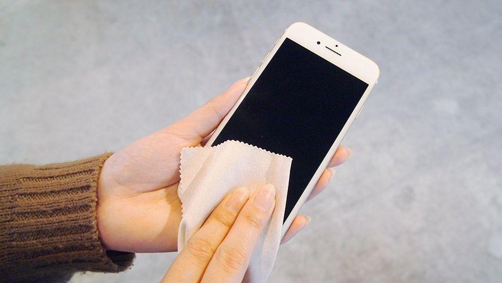 iPhone 7のホームボタンをクロスで拭いている