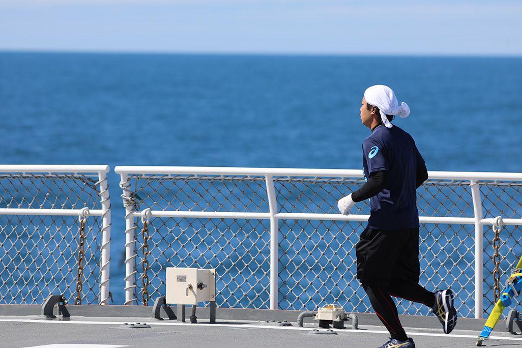 砕氷船「しらせ」の甲板でランニングをする男性