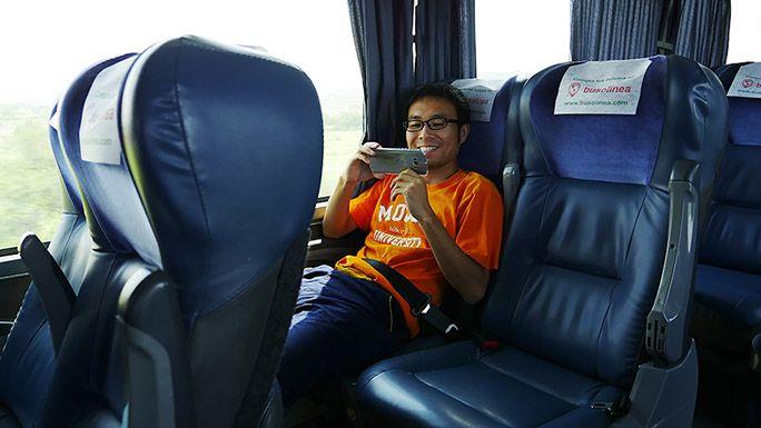 バスの中で楽しげにスマートフォンを利用する地主