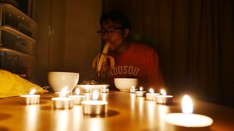 ろうそくだらけの部屋でバナナを食べる地主