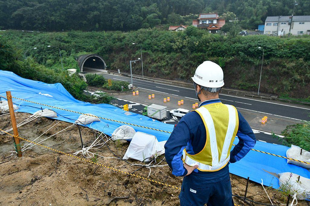 志和トンネルの復旧作業を見つめる作業着姿の男性