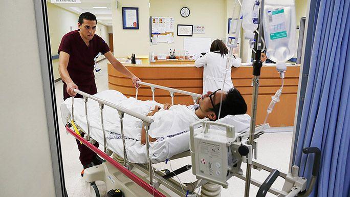 病院で検査のためベッドごと移動されている地主