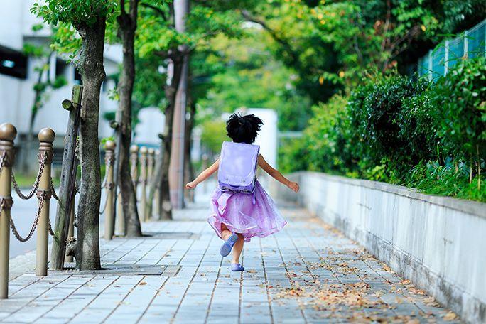 ひとりで学校へ向かうランドセルを背負った女の子