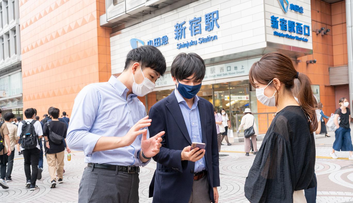 新宿駅西口でau5Gの通信エリアを調査をする人
