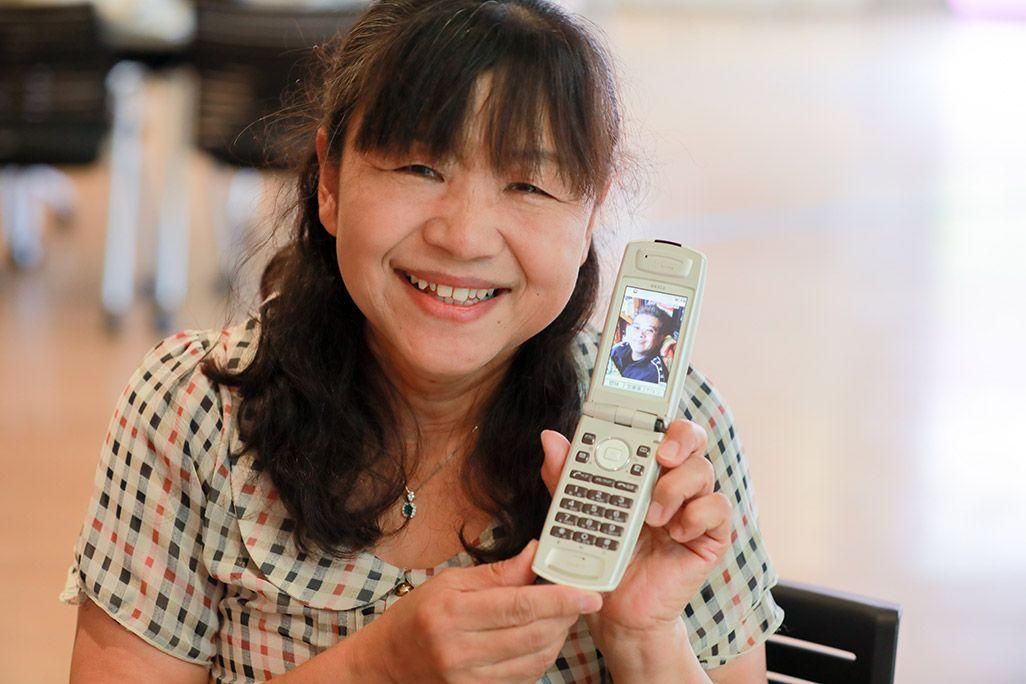 「おもいでケータイ再起動」で復活したケータイのディスプレイを掲げながら微笑む女性