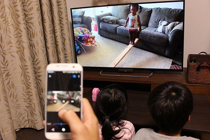 スマホとミラーリングしたテレビを見る子ども
