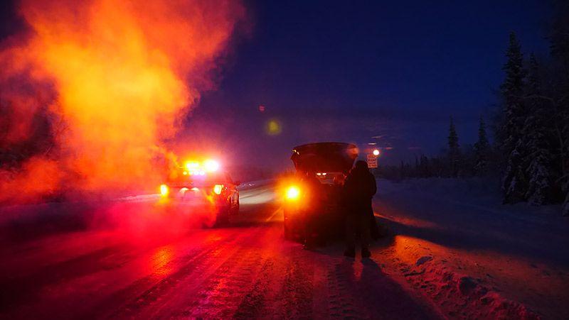 アラスカの道路で赤いランプで近づいてくる警察車両