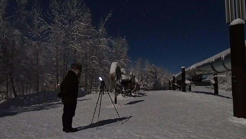 雪原にTORQUE G03を立てた三脚をのぞく地主