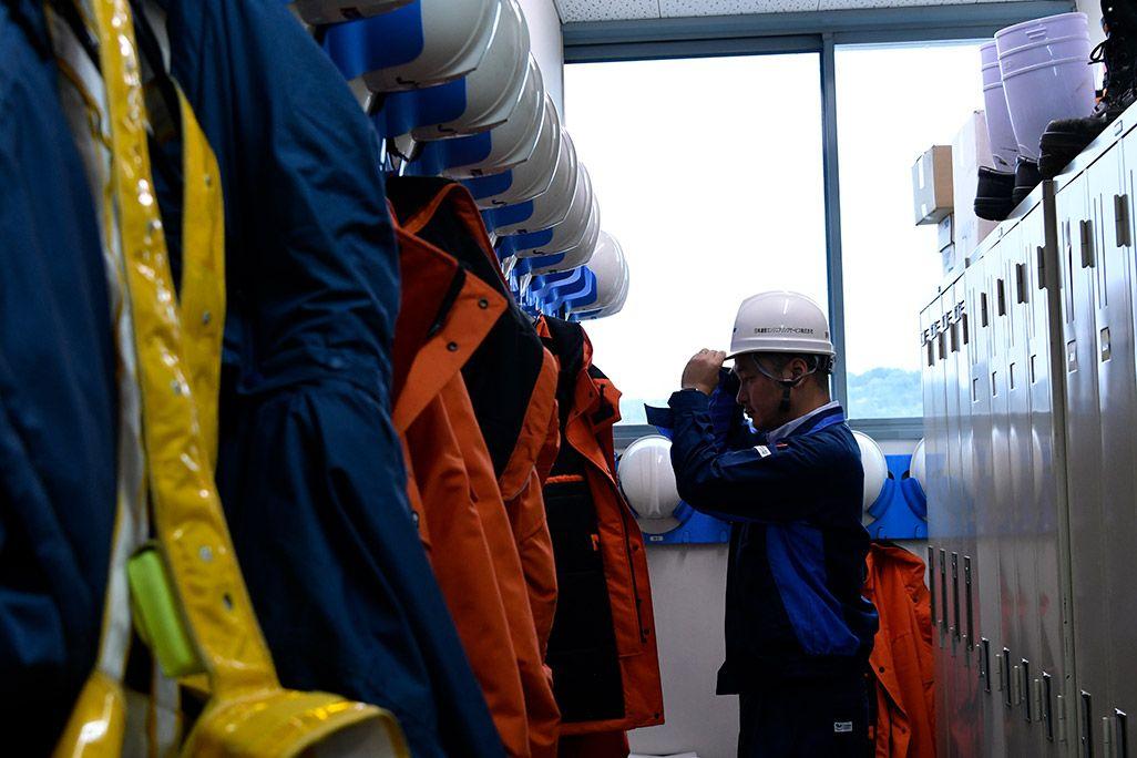 ロッカールームで作業着に着替え、ヘルメットを深くかぶる男性