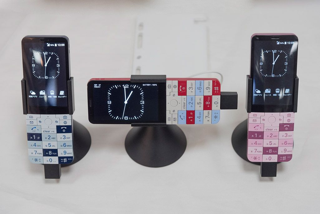 INFOBAR xvが3色勢ぞろい。中央が「置き時計モード」