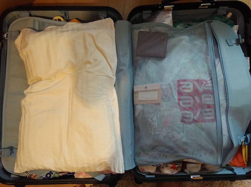KDDI・三戸が現地に持ち込むスーツケース。マイ枕が見える