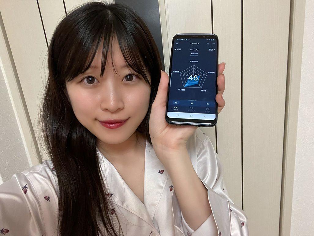 「睡眠モニター 01」で取得した睡眠スコアを見せる飯田菜々さん