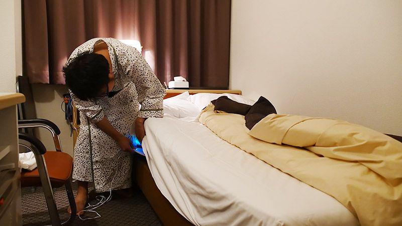 ホテルのマットレスの下に睡眠モニター 01をセッティングする地主