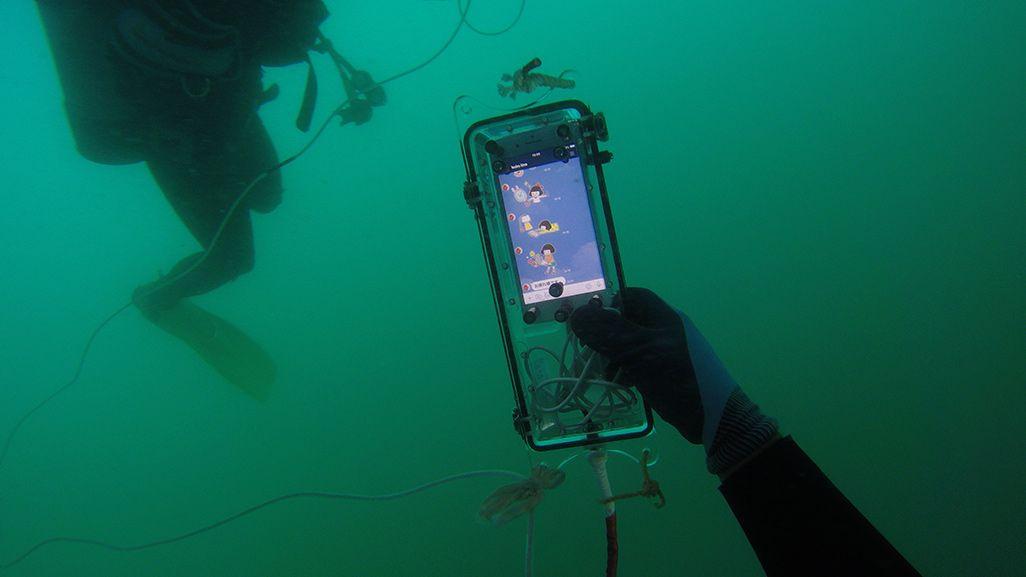 海中で防水パッケージに入ったiPhoneを手にしたダイバー