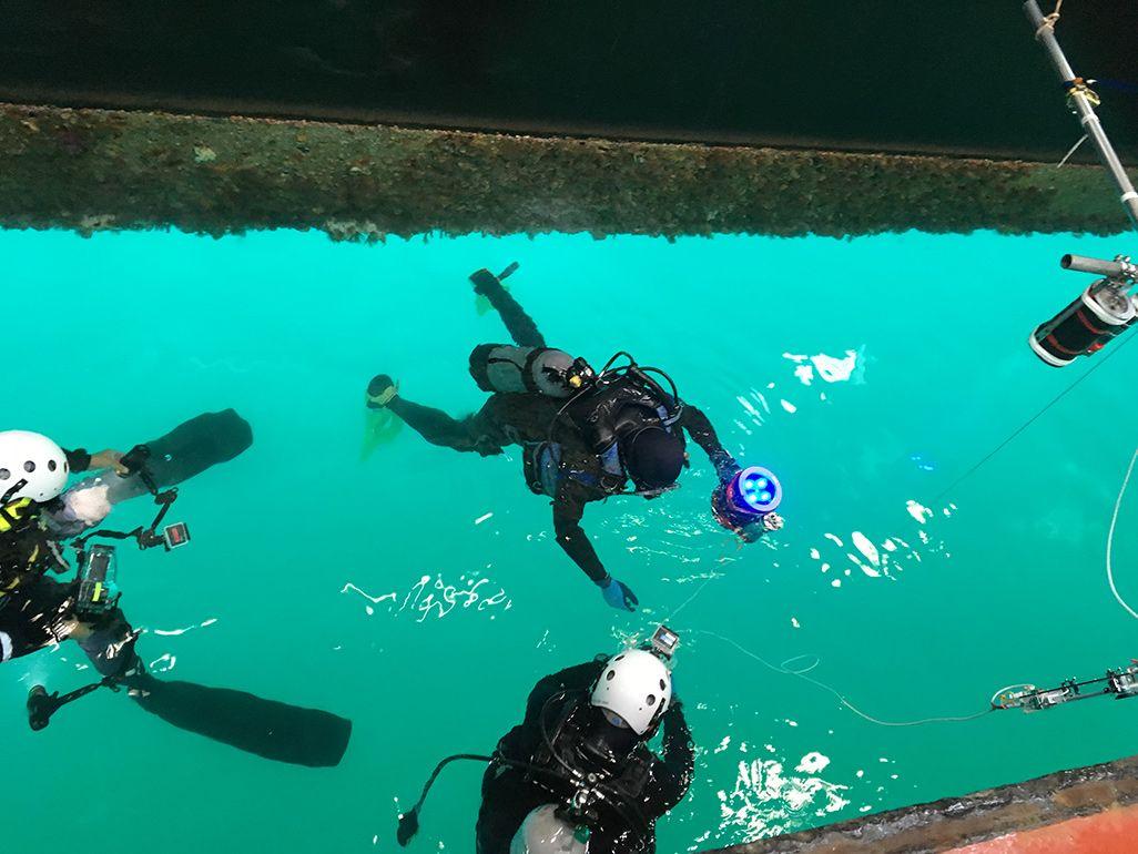 実験機器を手に潜水するダイバー