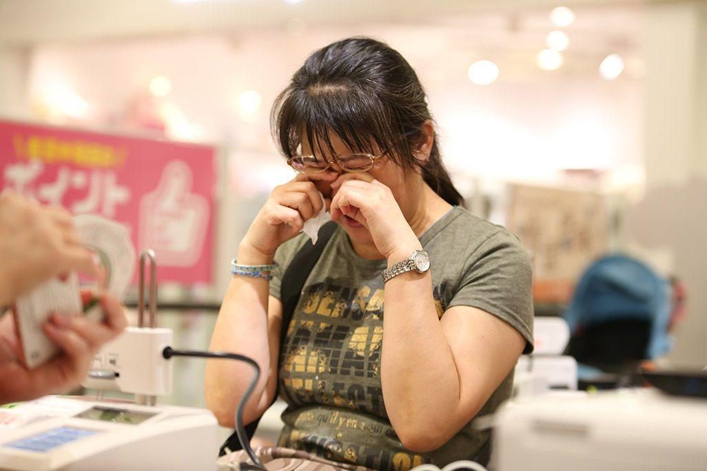 「おもいでケータイ再起動」でガラケーが復活し涙ぐむ女性