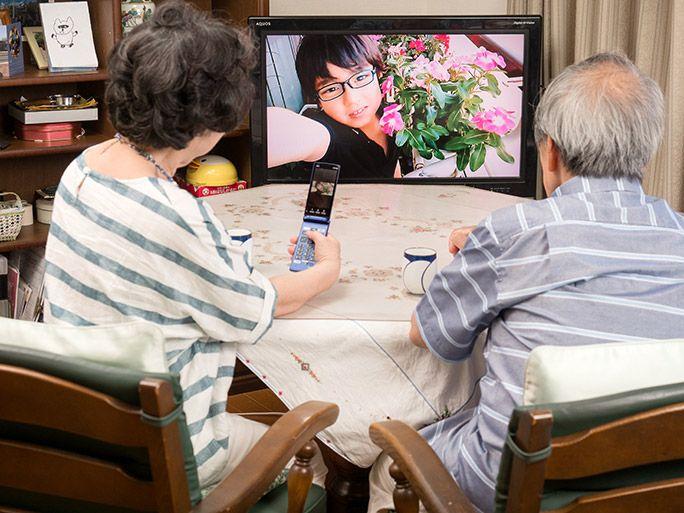 「テレビde写真」で孫の写真を眺める祖父母