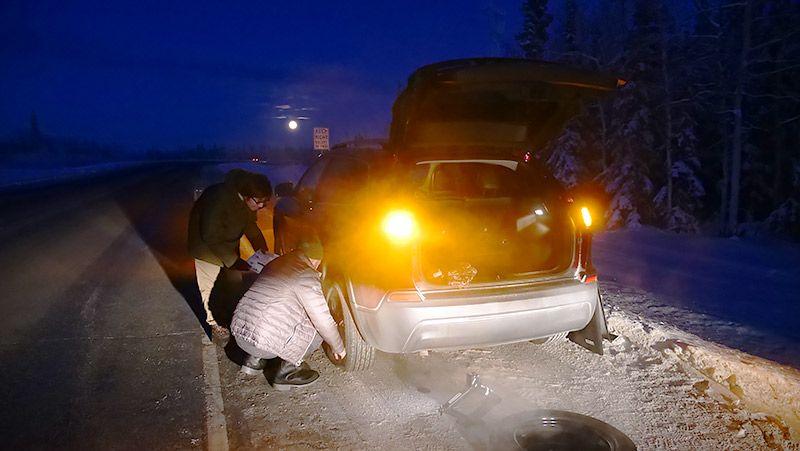 アラスカの道路でタイヤを交換する地主と助けてくれる現地の人