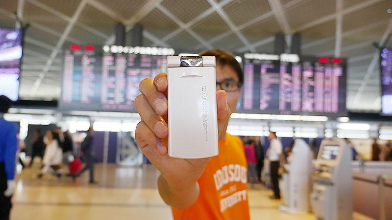 空港でガラケーをカメラに向けて持つ地主
