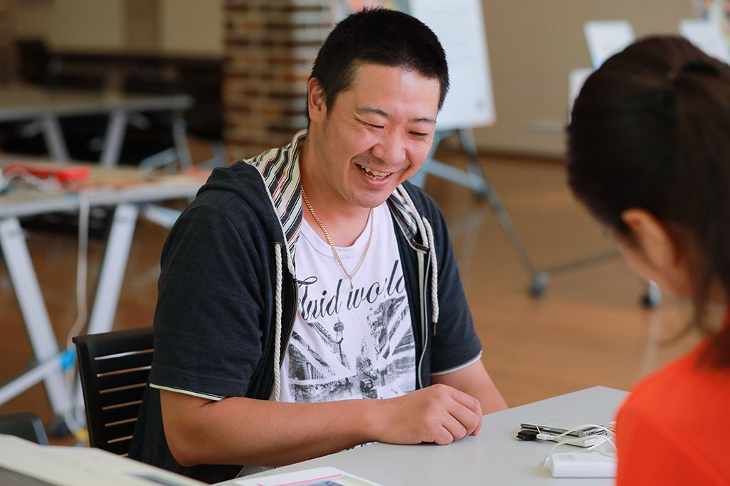 「おもいでケータイ再起動」で復活したケータイのディスプレイを見て微笑む男性