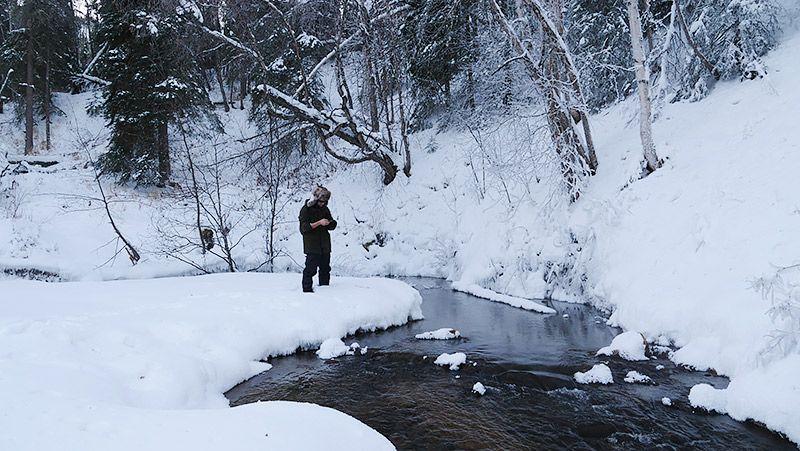 雪原の中に流れる川を眺める地主