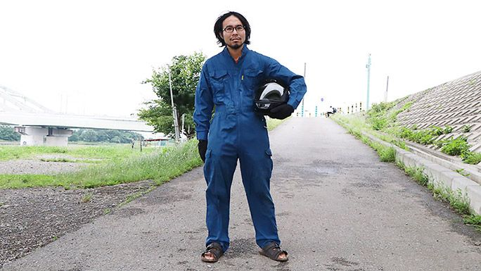 つなぎにヘルメットを抱え、河原でサンダルをはいているライターの地主