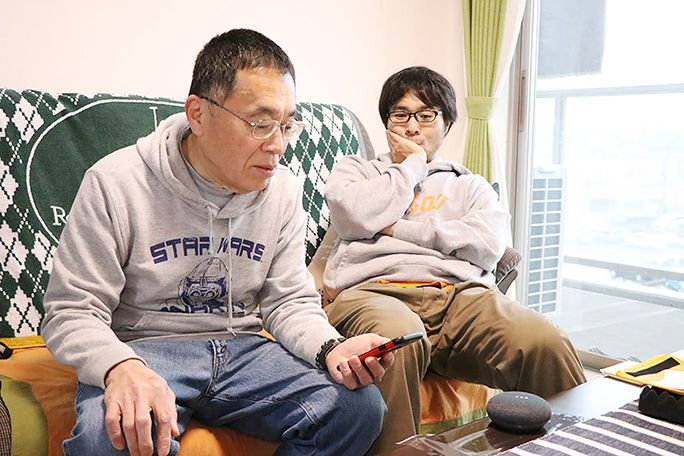 Google Home Mini を設定する父とヒマそうに眺める地主