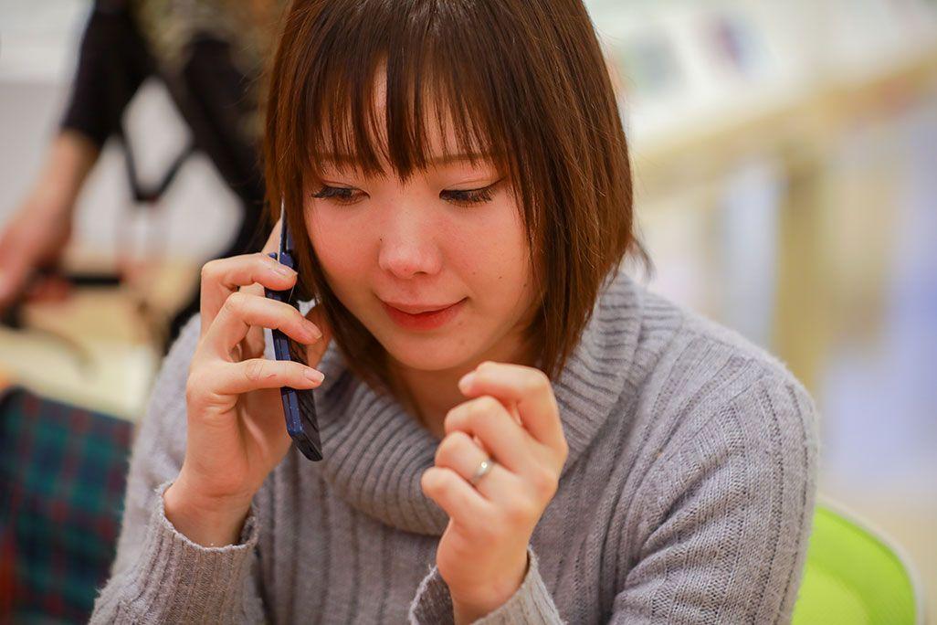 再起動したケータイに残された留守電を聞いて涙ぐむ女性