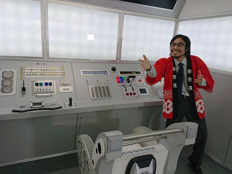 宇宙船を模したスタジオ内でハッピでポーズをとる地主