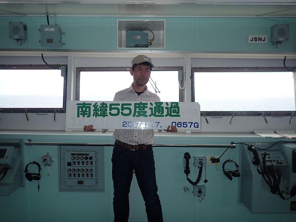 砕氷船「しらせ」の船内で「南緯55度通過」と書かれたプレートを手にする齋藤